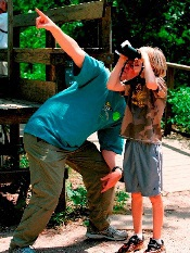 adult pointing, child looking through binoculars