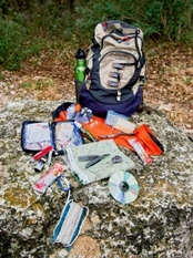 backpack with contents displayed on ground