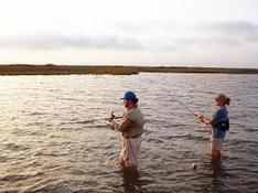 man and woman wade fishing on coast