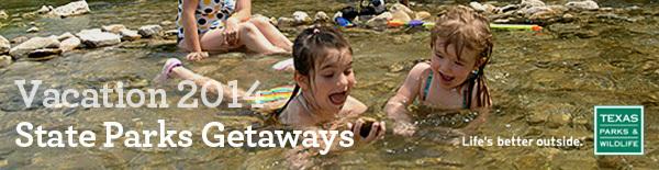 2 children splashing in creek, laughing