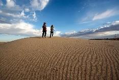 boy and girl running down sand dune