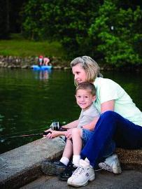 woman and happy boy fishing together, dock
