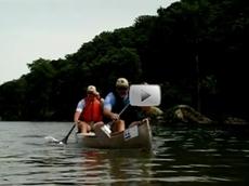 2 men paddling a canoe, river