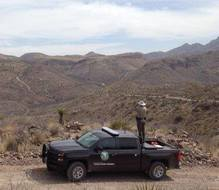 game warden standing on truck, viewing panorama
