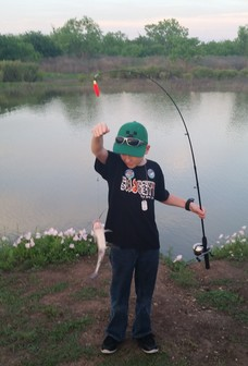 Boy holding catfish on fishing line.