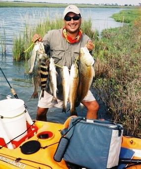 man holding stringer of flounder, redfish, etc. by kayak on coastal paddling trail
