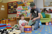 Dad pictured at a library reading to daughter