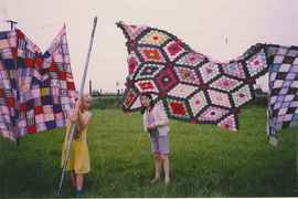 Children with quilts on a washing line