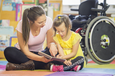 Disabled child and teacher