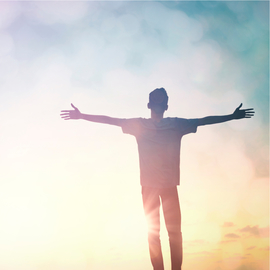 Man with arms outstretched in the sunlight