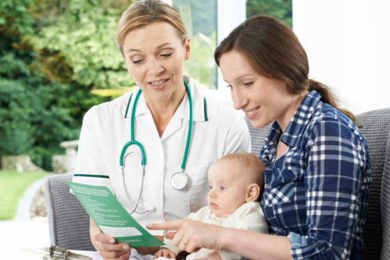 Health visitor with mother and baby image
