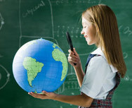 Child pointing at globe in classroom