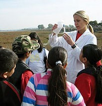 Teacher with students testing water in the field