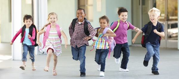 Young children wearing backpacks, smiling and running toward camera