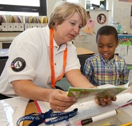 Wendy Spencer, CEO of CNCS, tutors a young student at an AmeriCorps service site.