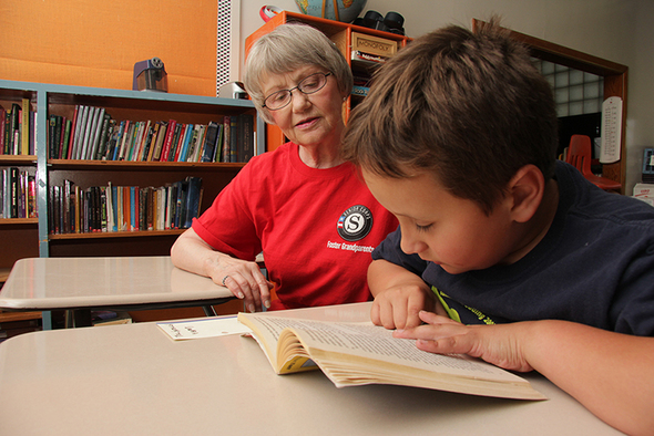 Senior Corps Foster Grandparent helps a student read in classroom.