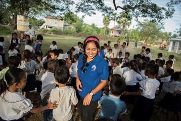 Peace Corps volunteer standing with children
