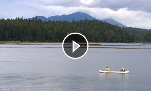 Video still of two people rowing a boat on a lake with mountains in the background.