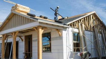 Construction worker on roof of house