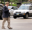 A man crossing the street while looking at his cell phone.