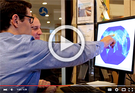 A screenshot of a new AEDT video shows Volpe staff pointing at a computer with a map on the screen.