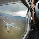 an image of a man looking out of a cockpit at a drone.