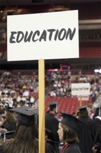 Education sign above graduates' heads