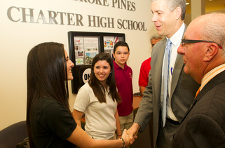 Arne shaking student's hand in front of charter high school sign