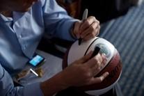 Arne Duncan signing a basketball