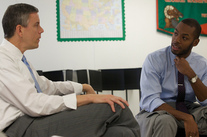 Arne Duncan speaking with a teacher