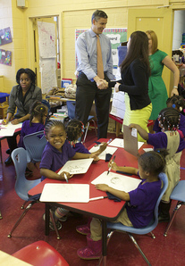 Arne Duncan talking with teachers while visiting a class