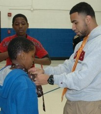"Columbia College student Alex Perez teaches elementary students how to tie neckties during a monthly Boys II Men ""Juniorversity"" session"