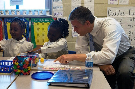Arne Duncan working with school children