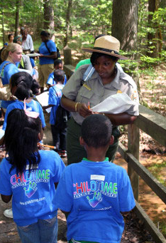 female park ranger talking to kids in park