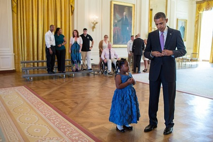 President Barack Obama writes a school excuse note for Alanah Poullard, 5, while visiting with Wounded Warriors and their families in the East Room du