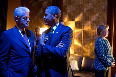President Barack Obama and former President Bill Clinton are bathed in blue light as they talk backstage prior to participating in the Clinton Global
