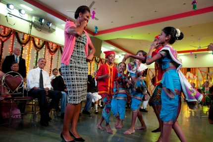 President Barack Obama watches as First Lady Michelle Obama dances with students during a Diwali candle lighting and performance at Holy Name High Sch
