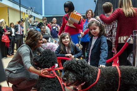 First Lady Michelle Obama, with Obama family pets, Bo and Sunny, greets children during a Christmas holiday program at the Children's National Medical