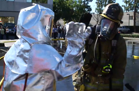 two people in safety suits for science experiments