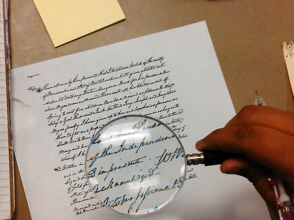 Students examining slave deeds under a magnifying glass