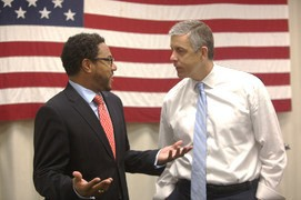 Arne Duncan speaks with an educator during a school visit.