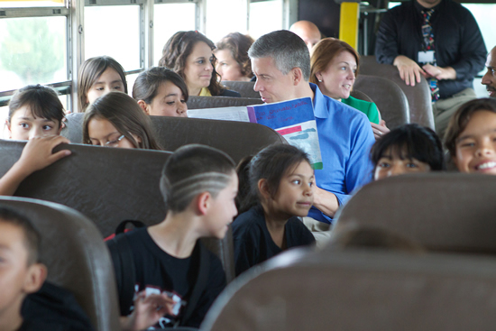 Secretary Duncan reading to students on bus