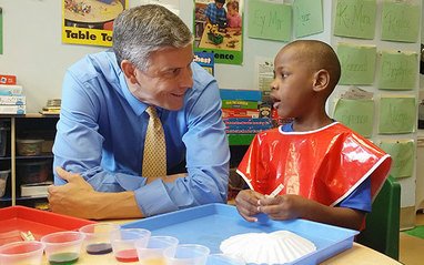 Secretary Duncan talking to young student.