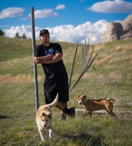 justin with dogs on prairie