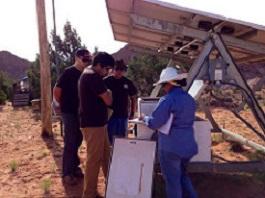 Photo of Sandia interns near a solar panel