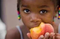 Little girl eating peach