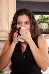 A woman drinks a cup of coffee.