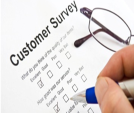 Picture of a customer survey with a pen in a hand checking a box. There is a pair of glasses next to the survey form..