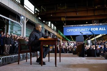 "President Obama signs a memorandum in front of a sign that says ""Opportunity for all"""