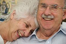 A smiling older couple sitting together.